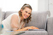 Smiling young woman laying on couch and using laptop