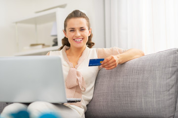 Happy young housewife with credit card making online shopping
