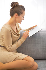 Young woman using tablet pc while sitting on divan