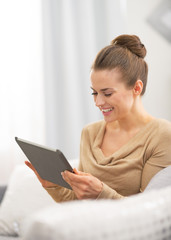 Smiling young woman using tablet pc while sitting on couch