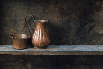 Copper jug and bowl on wood shelf
