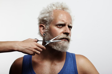 man with a woman's hand, cutting his beard