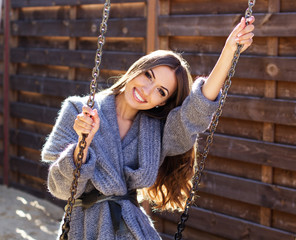 Young fashion girl having fun on swing