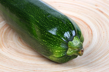Fresh zucchini vegetable on wooden plate