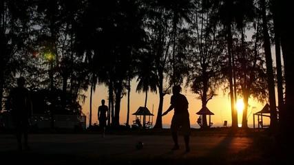 Football Match - Players Against Tropical Sunset near Beach.