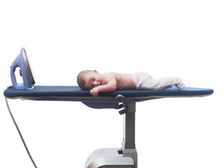 Small caucasian baby boy lying  on ironing system isolated