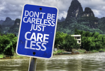 Don't Be Careless Just Care Less sign with a forest