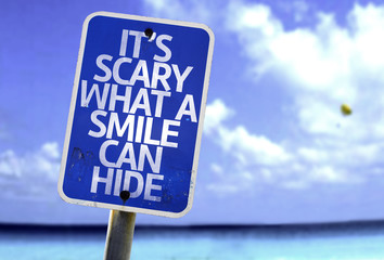 It's Scary What a Smile Can Hide sign with a beach