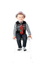 Smiling happy boy on stool studio shot isolated on a white backg