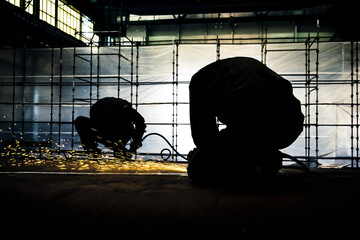 Two workers polishes part of the steel construction.