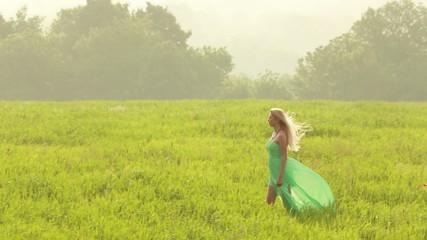 Blonde girl in green dress walking in the field
