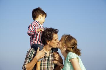 Padre con hijo subido en los hombros besando a su mujer