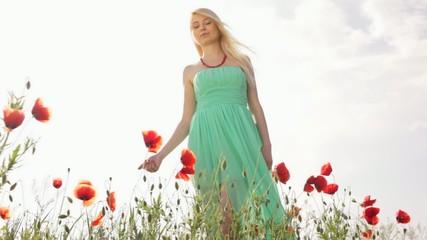 Blonde girl in green dress in poppy flower field