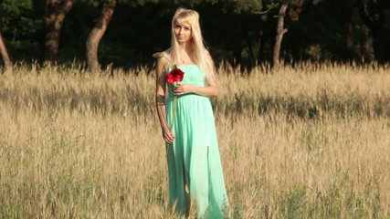Girl in green dress goes towards the camera with poppy flower