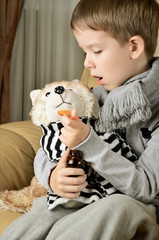 little boy feeds medicinal syrup the toy dog and says AAA