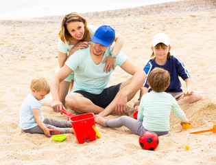 Smiling parens with three kids on sandy beach