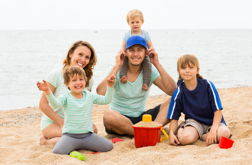 Positive parents with kids sitting at sandy beach