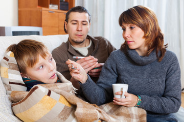 Loving parents giving medicinal syrup to teen son
