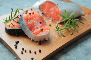 Salmon filets with fresh spices on wooden cutting board