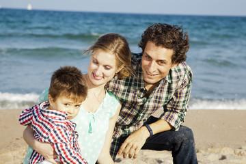 Familia disfrutando de su hijo pequeño en la playa