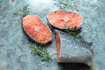 Salmon fillets with salt and rosemary on old metal board