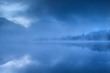 lake in Alps during misty morning