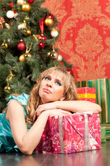 woman lies near the Christmas tree