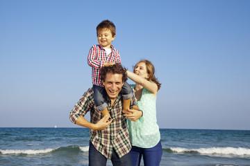 Niño riéndose y disfrutando con sus padres en la playa