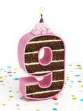 Number 9 shaped chocolate birthday cake with lit candle