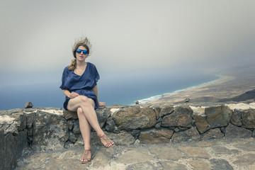 junge Frau sitzt auf einer Steinmauer
