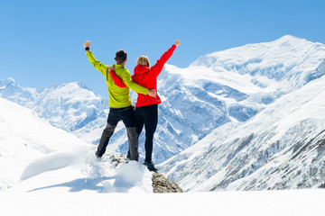 Hiking success, couple in winter mountains