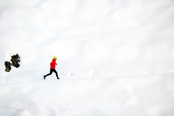 Woman running on snow in mountains