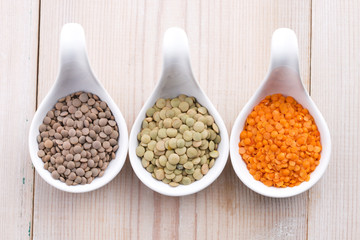 Three kinds of lentil in bowls - red lentil, green lentil and br