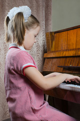 the girl schoolgirl learns to play a piano