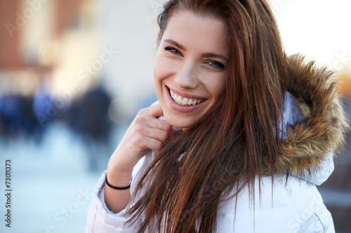 beautiful young woman smiling in winter time - 73011373