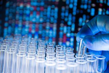 Gloved hand holds test tube against DNA background