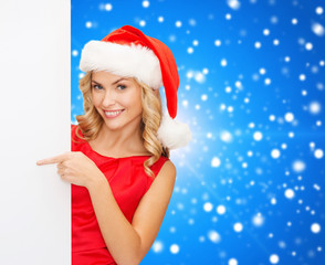 smiling young woman in santa hat with white board