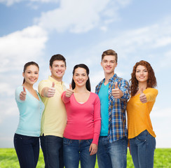 group of smiling teenagers over blue sky and grass