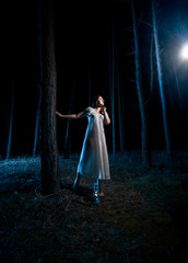 woman in white nightgown looking at ray of light at night forest