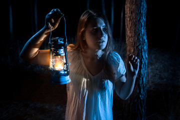 portrait ofnwoman lost in forest lighting the way with lantern
