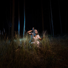 woman in nightgown sitting in high forest at night with lantern