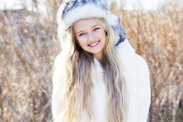 Cute little girl in winter clothes outdoors