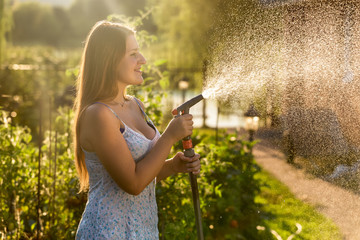 brunette woman holding hose pipe at garden at sunny day
