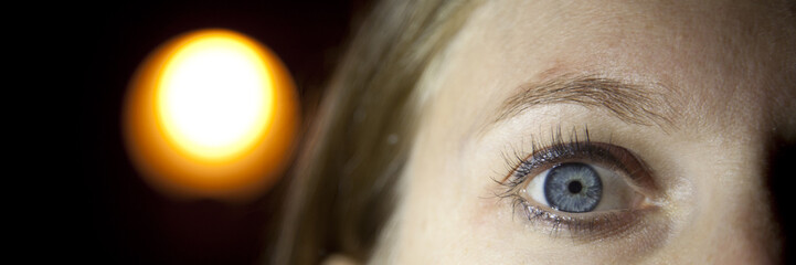Ojo azul de mujer con luz naranja al fondo