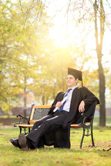 Relaxed graduate sitting on a bench in park