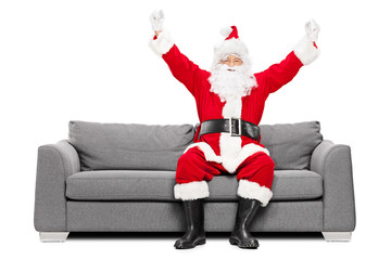 Santa Claus gesturing happiness seated on sofa