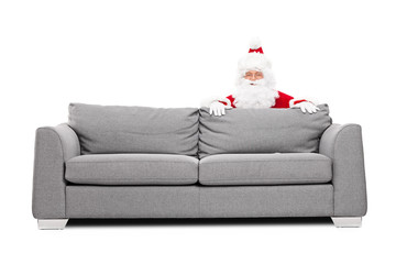 Santa Claus hiding behind a sofa
