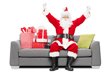 Santa gesturing happiness seated on sofa with gifts