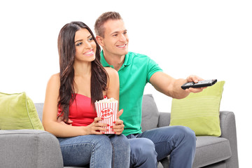 Young couple watching TV seated on a sofa