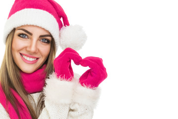 Beautiful Santa girl with hat gloves and scarf gesturing heart.